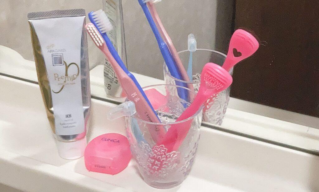 洗面台の上にある歯ブラシ、舌ブラシ、フロス、歯磨き粉
